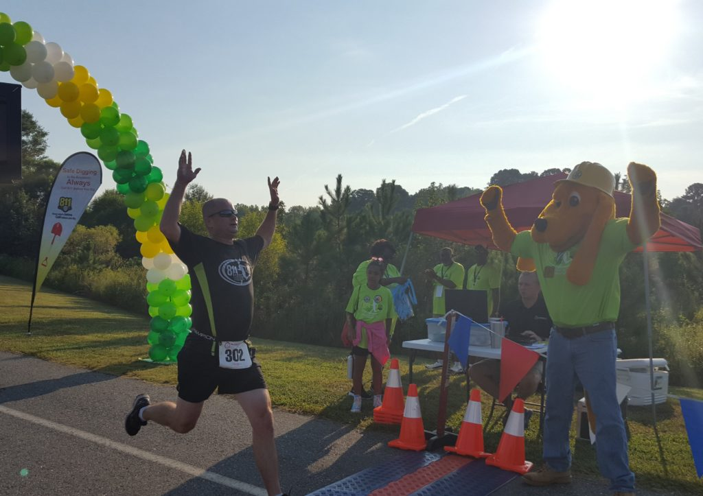 Digger cheering the first place winner of the 5K